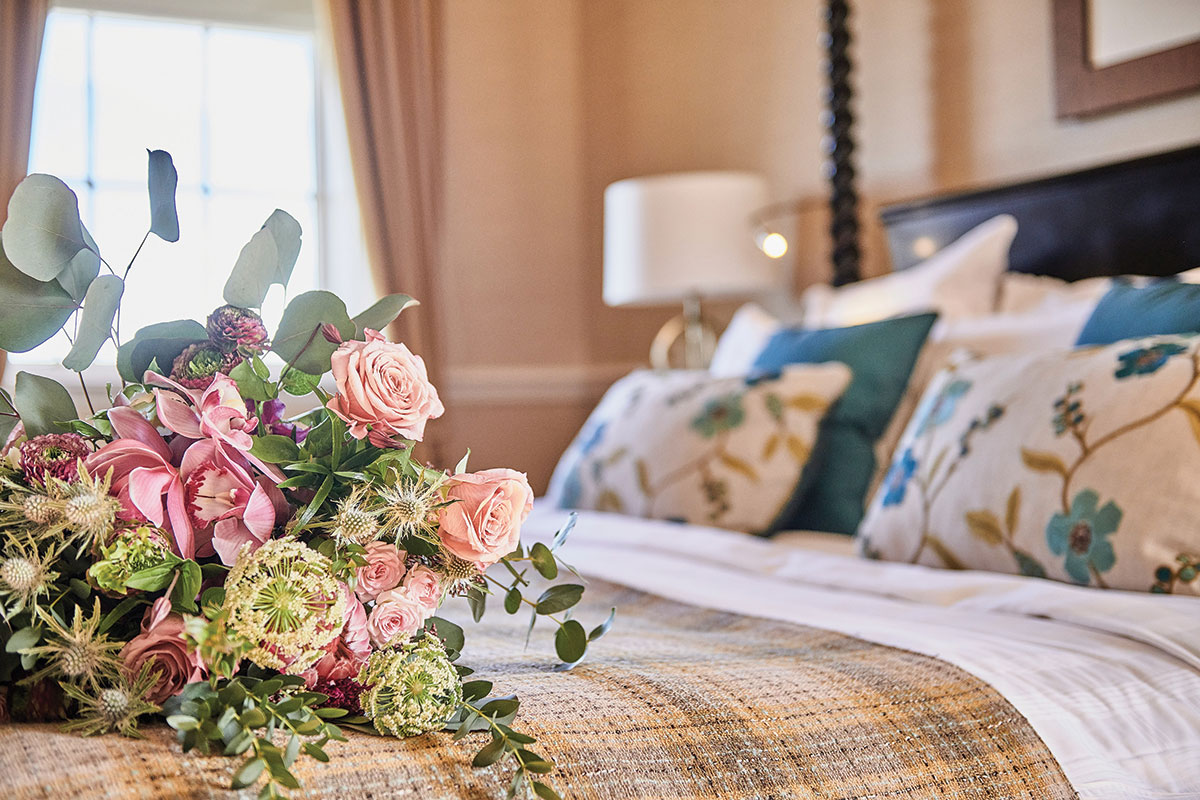 A bouquet of flowers on a bed in a suite at Dalmahoy Hotel and Country Club