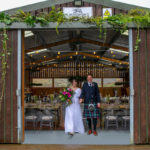 A couple stands at the entrance to the barn at Blackhouse Forest Etate