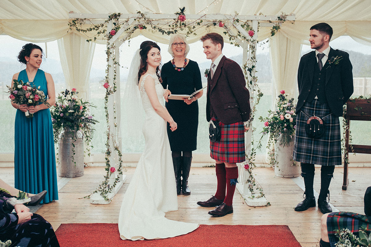 A bride and groom stand at the top of the aisle alongside a celebrant, a bridesmaid and a groomsman