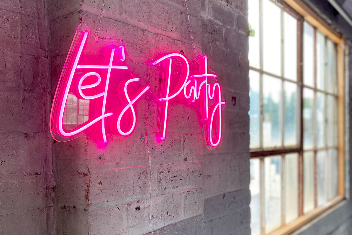 A pink neon 'Let's Party' sign