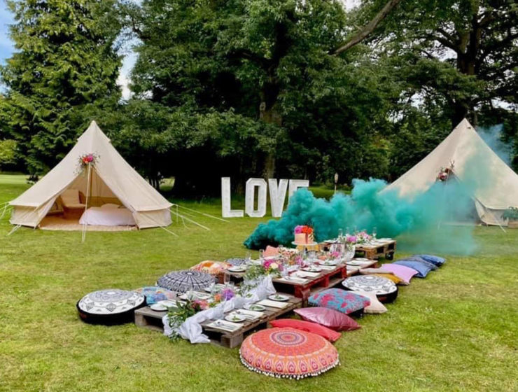 A boho outdoor reception set up with tents and cushions