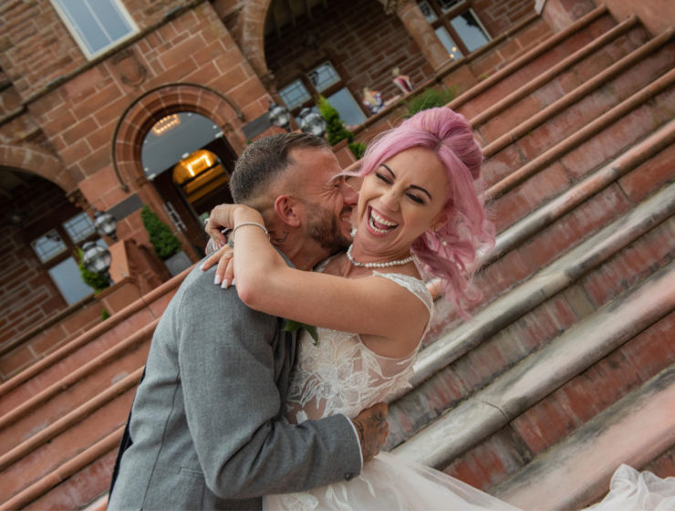 bride with pink hair and groom wearing grey kissing by the steps at Boclair House