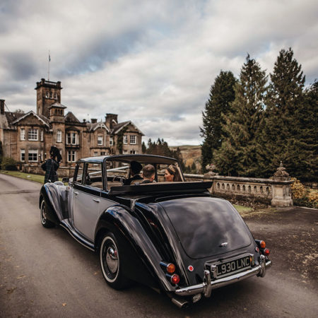 A vintage car with bride and groom in the driveway of Auchen Castle