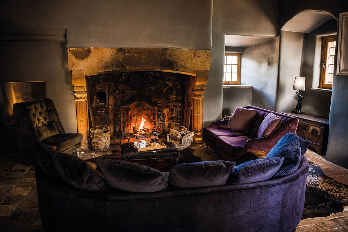 A fireplace and velvet seating at Aikwood Tower in the Scottish Borders