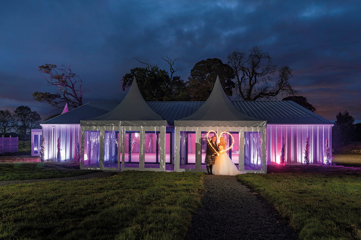 A bride and groom outside the marquee at Duntarvie Castle making love heart shape with sparklers
