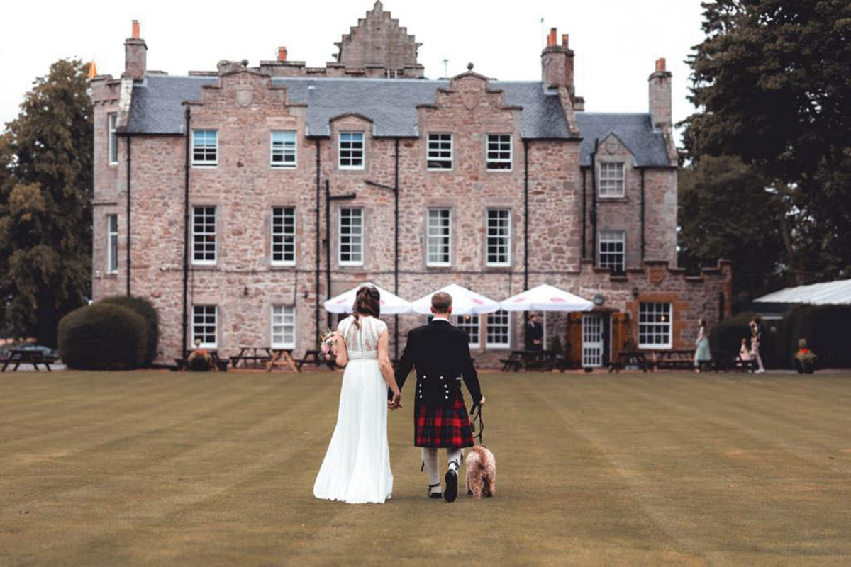 A bride and groom with a dog walking in the grounds of Shieldhill Castle