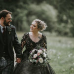 a bride wearing a black Zander wedding dress by Sottero and Midgeley holding hands with a groom wearing a kilt walking across a lawn